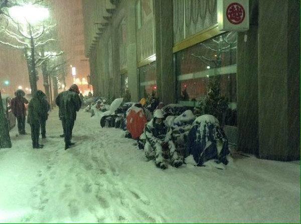 นาทีนี้เพื่อ ถุงโชคดี กับภาพสาวกแอปเปิล ยอมนั่งรอต่อคิว ไม่หวั่นแม้หิมะตก