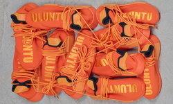 PW HU NMD สนีกเกอร์สีส้ม ที่มาพร้อมกับข้อความภาษาโคซาที่แปลว่า Human Race