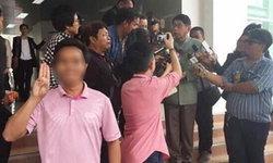 """ชายป่วนชู 3 นิ้วถ่ายรูปคู่ ขณะ """"วิษณุ"""" กำลังให้สัมภาษณ์สื่อ"""