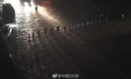 ปักกิ่งเจอฝนตกหนัก น้ำท่วมถนน ตร.จับมือเรียงเป็นกำแพงกั้นรถ
