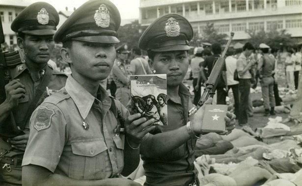 เจ้าหน้าที่ตำรวจแสดงหลักฐานเกี่ยวกับคอมมิวนิสต์ที่ได้จากการจับกุมนักศึกษาในเหตุการณ์ 6 ตุลาคม พ.ศ.2519