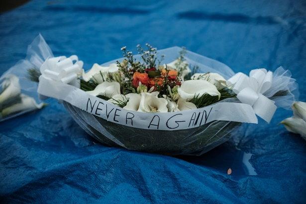 ตะกร้าดอกไม้พร้อมสโลแกน Never Again เนื่องในวันครบรอบ 25 ปี เหตุการณ์ฆ่าล้างเผ่าพันธุ์ในรวันดา