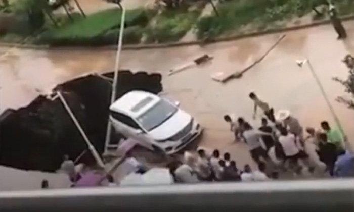 หลุมยักษ์โผล่กลางถนน ชาวจีนรวมพลังฉุดรถยนต์ออกจากปากหลุม