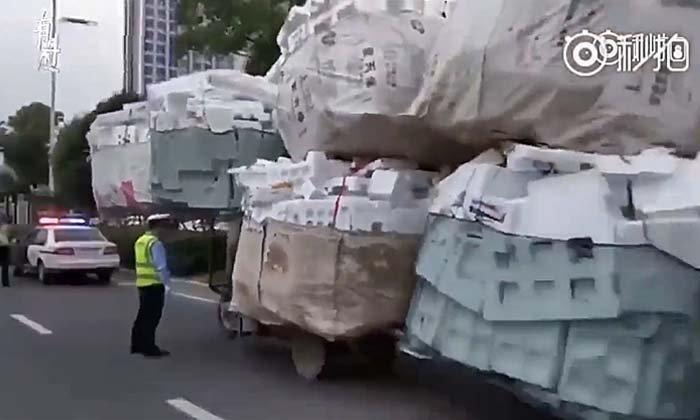 นึกว่ารถบรรทุก! ตำรวจจราจรจีนจับสามล้อขนของมากเกินเกณฑ์
