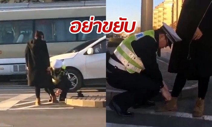 ชาวเน็ตเป็นปลื้ม ตำรวจจีนก้มผูกเชือกรองเท้าให้หญิงท้อง กลางถนน