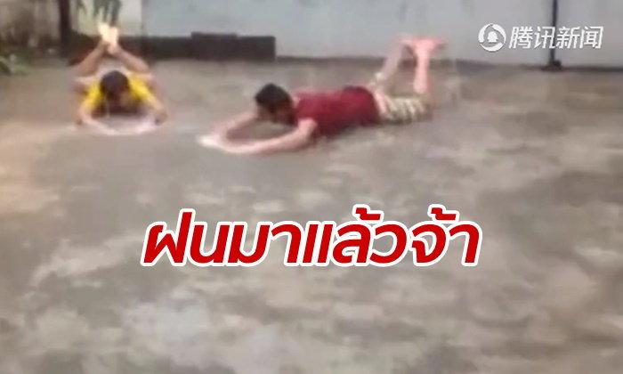 สองชายสุดดีใจ นอนว่ายน้ำท่ากบกับพื้น หลังฝนตกช่วยคลายร้อนในยูนนาน