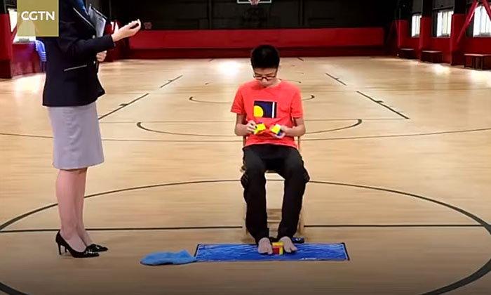 """ขั้นเทพ! เด็กจีนวัย 13 ใช้มือ-เท้าแก้ """"รูบิก"""" สามอันพร้อมกันเร็วสุดในโลก"""