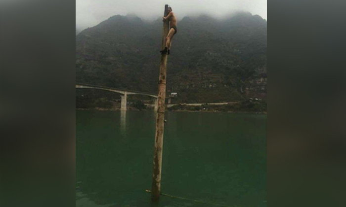 ชายแก้ผ้าปีนเสาไม้กลางน้ำ เมาหลอนโวยวายถูกไล่ฆ่า