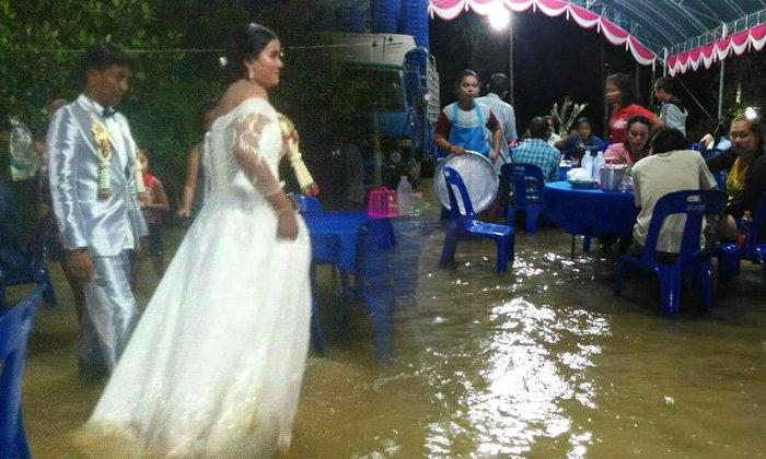 น้ำท่วมไม่ใช่อุปสรรค คู่บ่าวสาวใส่ชุดสวย ลุยน้ำฉลองวิวาห์