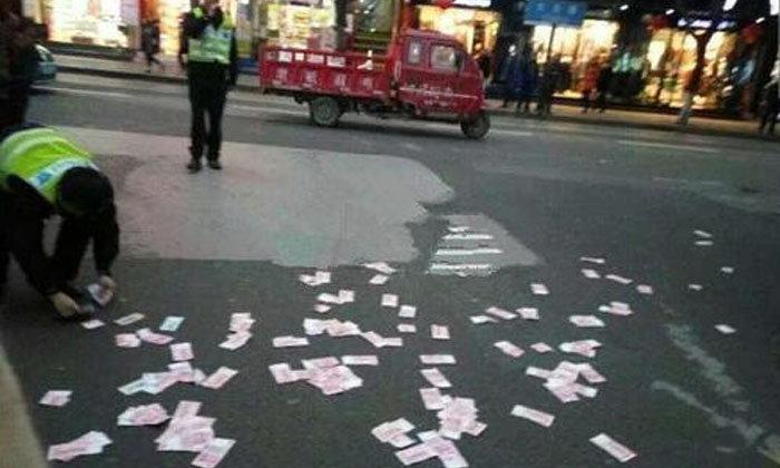 หญิงชาวจีนโปรยเงินทิ้งกลางถนน เดือดร้อนตำรวจช่วยเก็บ
