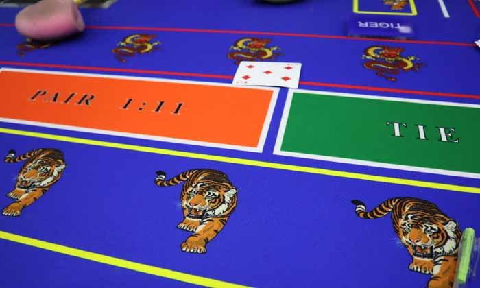 """ซุ่มจับเซียนพนันกว่า 50 คนล้อมวงแทง """"ไพ่เสือมังกร"""" เงินสะพัดหลายแสน"""