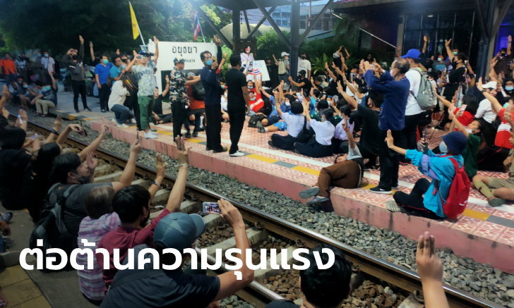 คณะราษฎรอยุธยา ชู 3 นิ้ว นั่งเคารพธงชาติบนสถานีรถไฟ หลังนักเรียนถูกป้าตบเพราะไม่ยืน