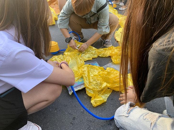 ปลุกน้องมาสู้: ผู้ชุมนุมเป่าลมเป็ดยางสีเหลือง ที่เป็นสัญลักษณ์หนึ่งของการชุมนุม ระหว่างการชุมนมที่ห้าแยกลาดพร้าว ในกรุงเทพมหานคร วันที่ 27 พ.ย. 2563
