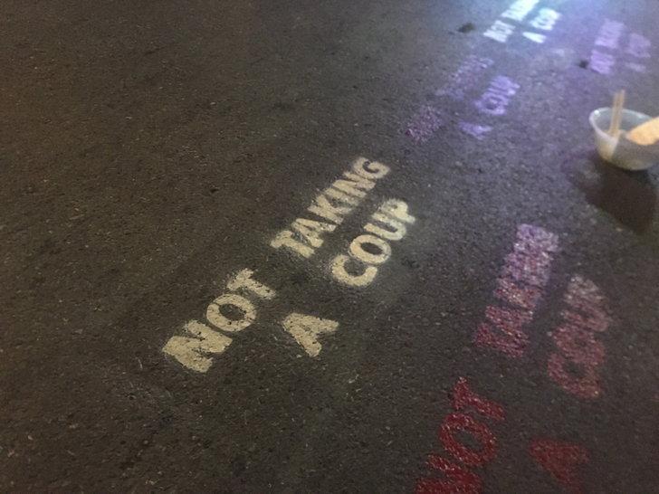พ่นข้อความ: ผู้ชุมนุมพ่นสีเป็นข้อความต่อต้านการรัฐประหารเป็นภาษาอังกฤษว่า Not taking a coup บนถนนบริเวณห้าแยกลาดพร้าว ระหว่างการชุมนุมเมื่อวันที่ 27 พ.ย. 2563