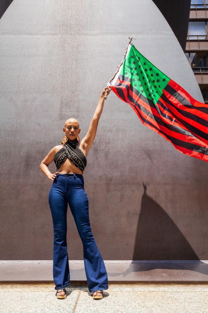 ภูมิใจเสรีภาพ: นางสาวคียา แทรมเมลล์ ศิลปินด้านการแสดง โบกธงอิสรภาพคนผิวดำระหว่างการเดินขบวนมิลเลียนแมน เมื่อวันที่ 19 มิ.ย. 2563 ในเมืองชิคาโก รัฐอิลลินอยส์ ในวันจูนทีนธ์ ที่รำลึกเหตุการณ์เมื่อวันที่ 19 มิ.ย. 2408 เมื่อกองทัพสหภาพ (ฝ่ายเหนือ) อ่านคำสั่งที่เมืองแกลวิสตัน รัฐเทกซัส ให้ปลดปล่อยทาสทั้งหมดในรัฐเทกซัสตามกฎหมายส่วนกลางของสหรัฐ