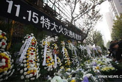 ภาพชาวจีนร่วมไว้อาลัยเหยื่อตึกไฟไหม้ 58 ศพ