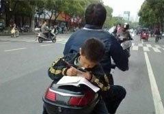 พ่อแม่รังแกฉัน! ภาพเด็กจีนทำการบ้าน บนรถมอเตอร์ไซด์