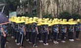 สดใสวันฝนพรำ นักเรียนจีนใส่ร่มกันฝนจานบินฝึกทหาร