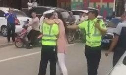 โดนเข้าให้! ตำรวจจีนถูกหญิงโอบคอบังคับจูบกลางถนน
