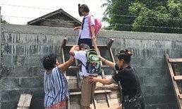 สุดเวทนา! สองพี่น้องคู่แฝดปีนกำแพง ลุยน้ำท่วมไปโรงเรียน