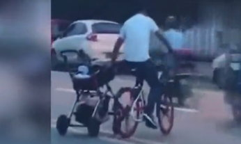 หวาดเสียว! ชายขี่จักรยานมือเดียวข้ามถนน อีกมือลากรถเข็นเด็ก