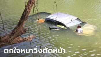 สาวตกใจสุนัขตัดหน้ารถ หักกระบะพุ่งลงคลองจมมิดทั้งคัน โชคดีออกจากรถทัน