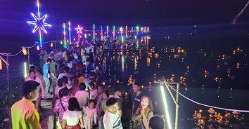 นักท่องเที่ยวพาคู่รักและครอบครัวมาร่วมลอยกระทงโฮมฮัก บนสะพานไม้แกดำ(ชมภาพมุมสูง)