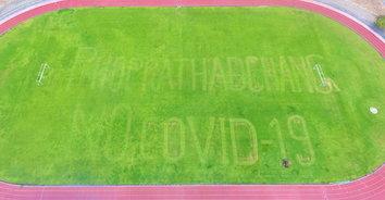 ไอเดียแจ่ม! ตัดหญ้าสนามฟุตบอลเป็นอักษรโควิด