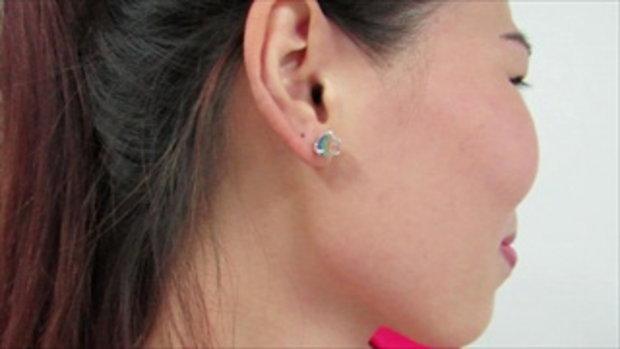 หญิงสาวในชุดสีแดงจะแสดงให้คุณเห็นในรูปแบบใหม่ของต่างหู