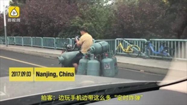 ผู้ใช้ถนนจีนเสียว คนส่งถังแก๊สเล่นมือถือขณะขับมอเตอร์ไซค์