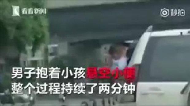 สุขาเคลื่อนที่? ชายจีนอุ้มเด็กให้ปัสสาวะออกนอกหน้าต่างรถยนต์