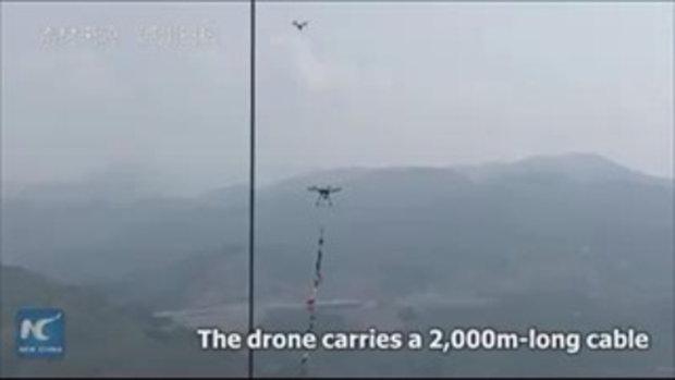 """อย่างเจ๋ง วิศวกรจีนใช้ """"โดรน"""" ลากสายเคเบิล เชื่อมสะพานแขวนยาวที่สุดในเอเชีย"""