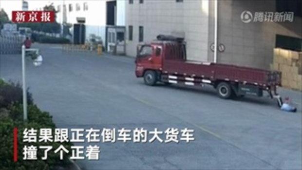 หนุ่มจีนเดินเล่นมือถือ ถูกรถบรรทุกถอยหลังชนล้มตีลังกา หวิดโดนเหยียบซ้ำ