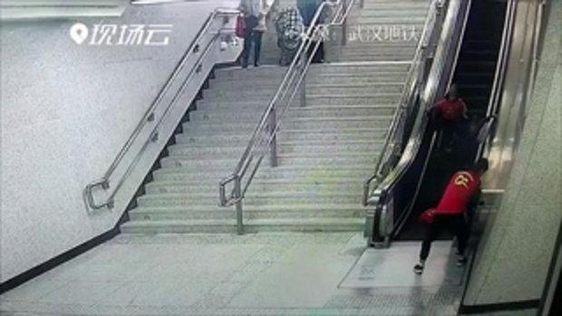 อาสาสมัครรถไฟจีนพุ่งสุดตัวช่วยคนตกบันไดเลื่อน จนตัวเองลื่นล้มบาดเจ็บ