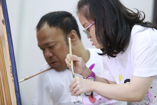 เหมียวและคุณเอกชัย วรรณแก้ว ศิลปินผู้พิการ ร่วมกันวาดภาพประกอบดนตรีในพิธีเปิดนิทรรศการจากดาวน์สู่ดาว